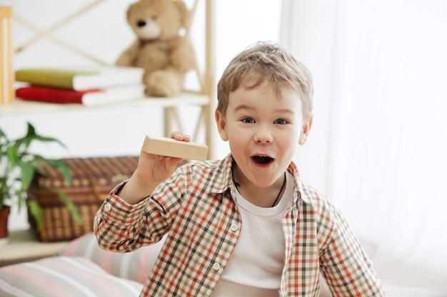 床に座っている小さな子供。家で木製の立方体で遊んでいるかなり笑顔の驚いた少年。コピーまたはネガティブスペースのある概念的なイメージ。