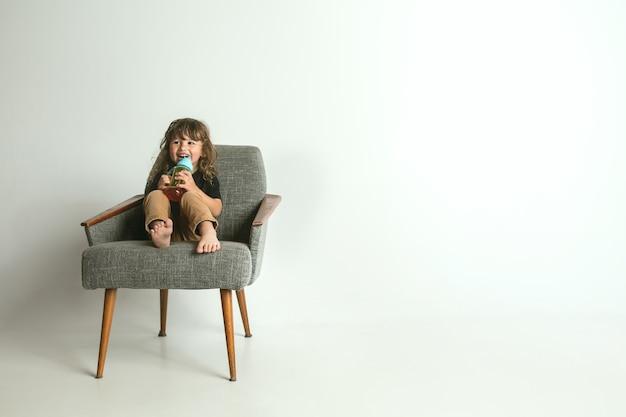 Piccolo bambino seduto e giocando in poltrona isolato sulla parete bianca dello studio
