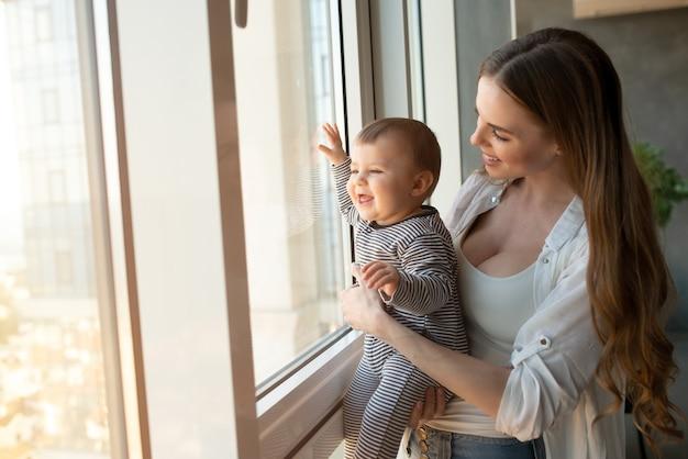 小さな子供は笑顔でお母さんに満足