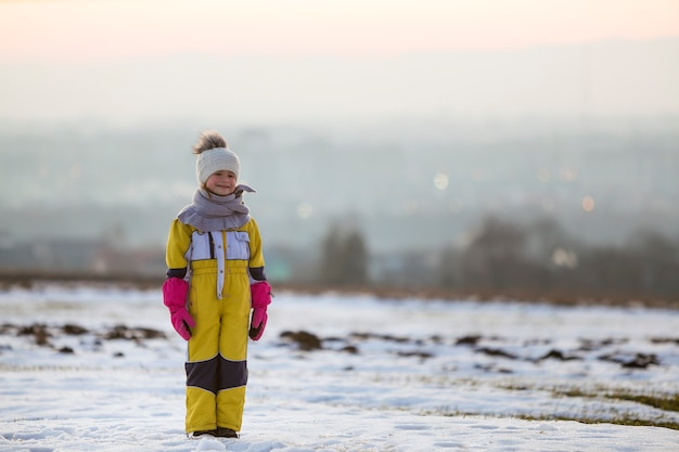 Little child standing outdoors on snow covered field