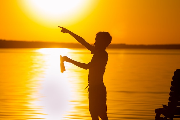 A little child stands on the lake at sunset. in the left hand he holds a paper airplane, and with the right hand he points with his finger into the distance