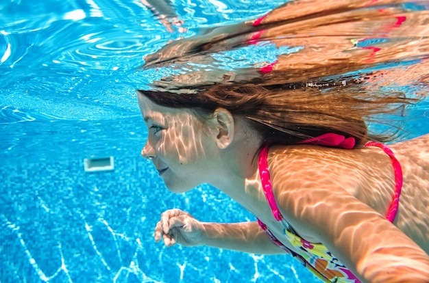 Little child swims underwater in swimming pool, happy active baby girl dives and has fun under water