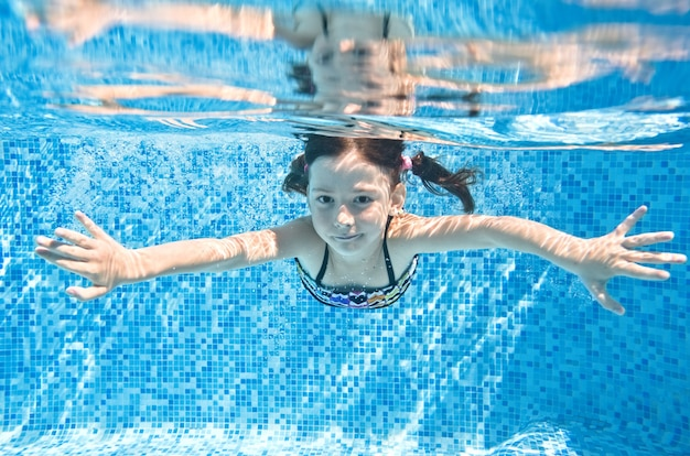Little child swims underwater in swimming pool, happy active girl dives and has fun under water, kid fitness and sport