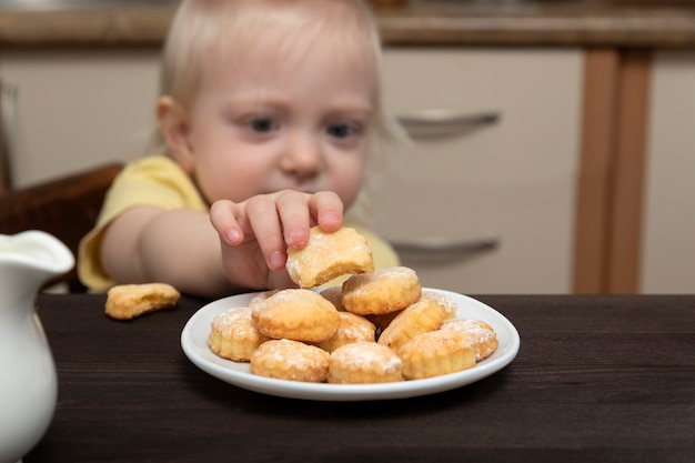 작은 아이가 접시에서 쿠키를 걸립니다.