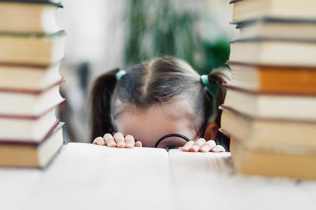 小さな子供は本の山を読むことからテーブルの下に隠れようとします。子供の教育の概念。