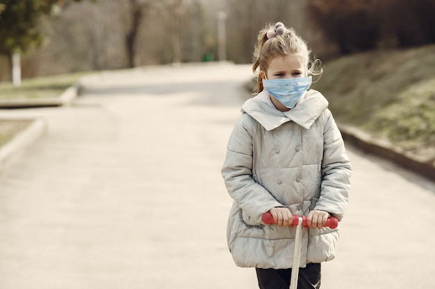 Little child walks outside in a mask
