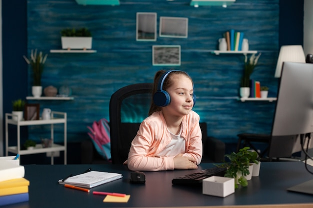 Little child wearing headphones having online math lesson on computer