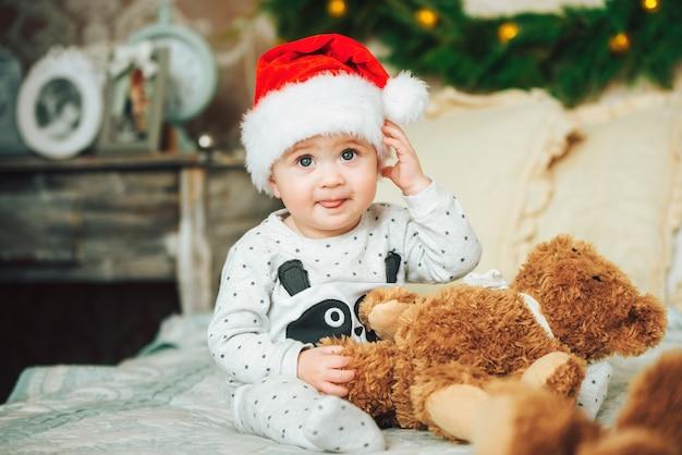 Маленький ребенок в красной рождественской шапочке забавно показывает язык
