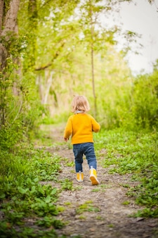 Little child wearing yellow rain boots, walking along a forest path in the grass