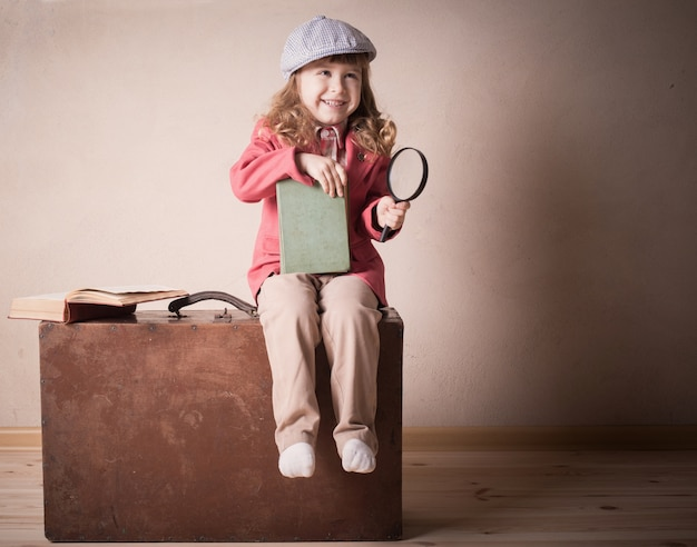 Little child with book on suitcase indoor