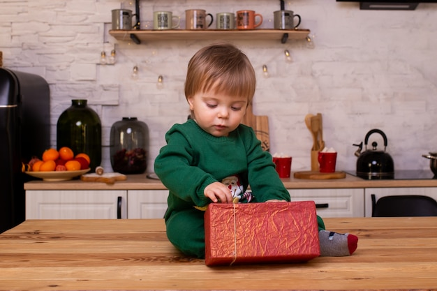 Little child with christmas gift in kitchen at home.