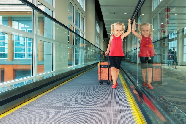Little child with luggage stand on airport transit hall walkway moving to plane departure gate for waiting flight boarding.
