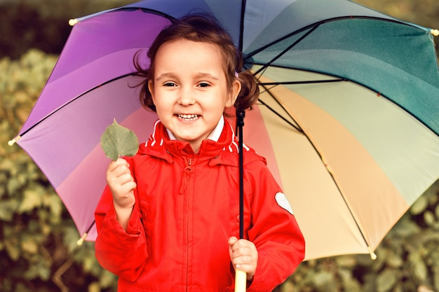 Little child with multicolored rainbow umbrella outdoors