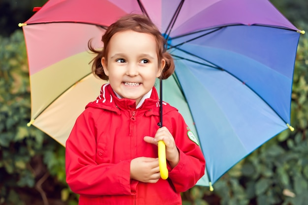 Little child with multicolored rainbow umbrella outdoors.