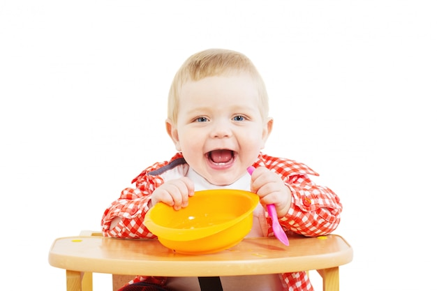 Маленький ребенок с тарелкой и ложкой на белом