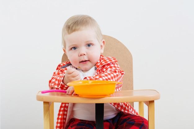 Маленький ребенок с тарелкой и ложкой на белой стене