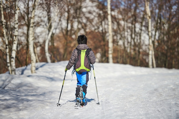 Little child with touring skis in snowy road
