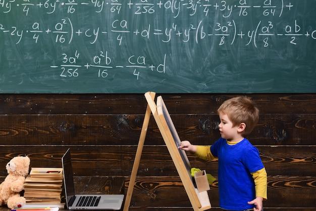 칠판에 쓰는 작은 아이. 수학 방정식으로 보드 앞에 아이. 수학을 공부하는 똑똑한 학생