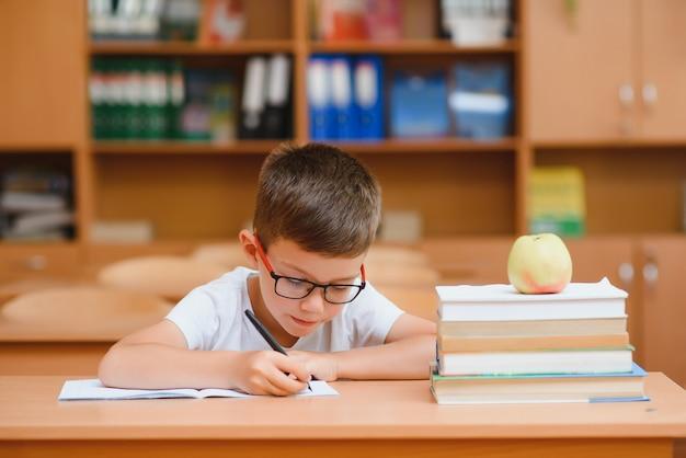 Маленький ребенок писать с красочными карандашами, в помещении. начальная школа и образование. ребенок учится писать буквы и цифры.