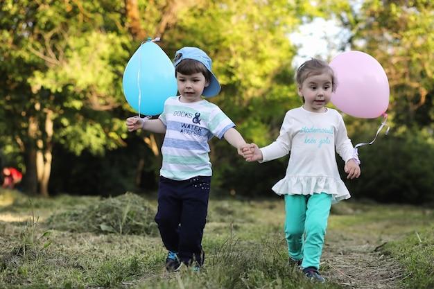 小さな子供たちが風船のある公園を歩いています