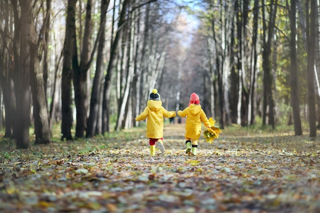Маленькие дети гуляют в осеннем парке под опаданием листвы
