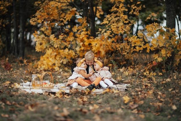 秋の公園でのピクニックで小さな子供たち。彼らは格子縞の上に座って抱きしめています。
