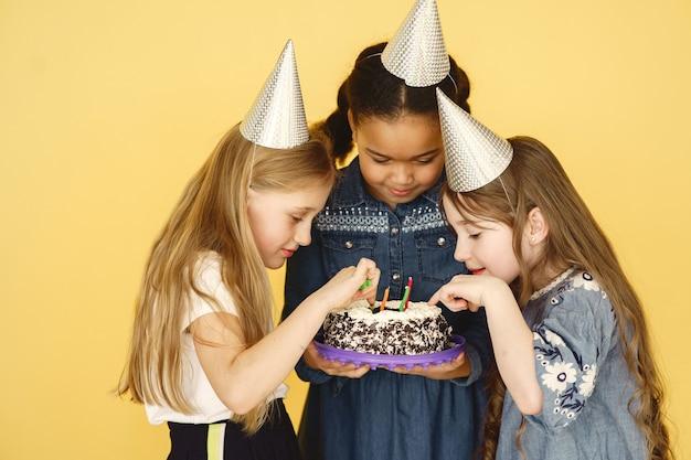День рождения маленьких детей, изолированные на желтой стене. дети держат торт.