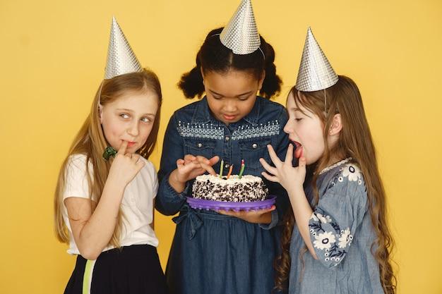 노란색 벽에 고립 된 작은 아이 생일. 케이크를 들고 아이.