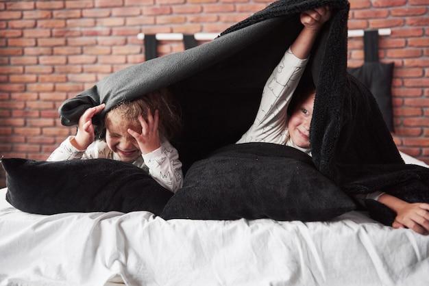 Маленькие дети, мальчик и девочка, лежа и играя с подушками на покрывало с одеялом