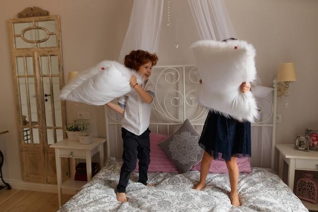 어린 아이, 소년과 소녀는 침대에 베개를 가지고 노는.