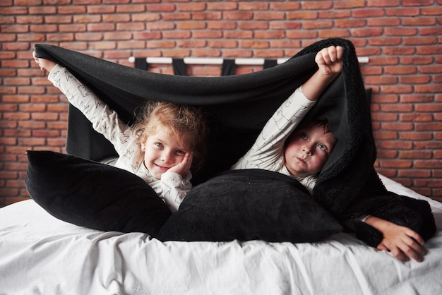 Little children, boy and girl laying and playing with pillows on the bed cover with a blanket