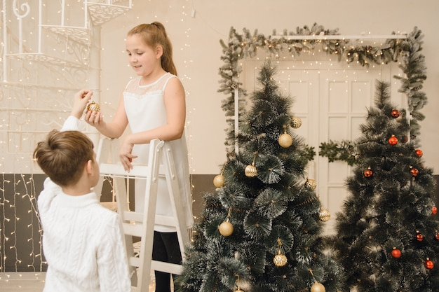 Little children decorate  christmas tree in a bright interior. girl  boy, bror  sister hang  toys on  branches of spruce. family christmas