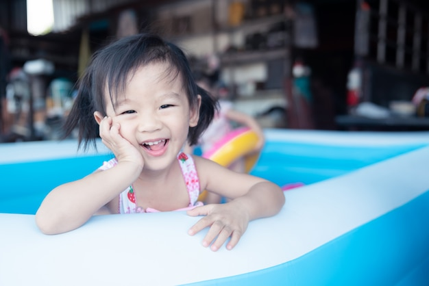 Little children enjoy and have fun playing water in inflatable pool