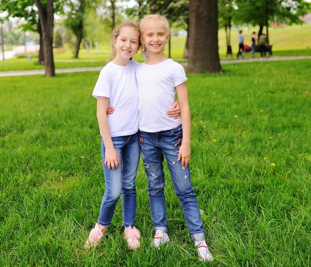 작은 어린이 여자 친구 웃 고, 공원에서 녹지.