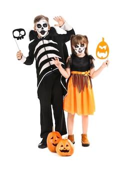 Little children in halloween costumes on white