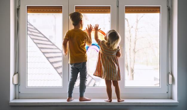 창에 무지개를 그리는 배경에 있는 어린 아이들 집에서 아이들이 여가를 즐기는 사진
