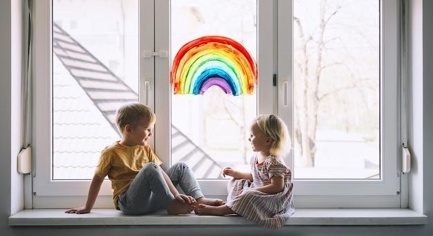 家での子供の余暇の窓の写真に虹を描く背景に小さな子供たち