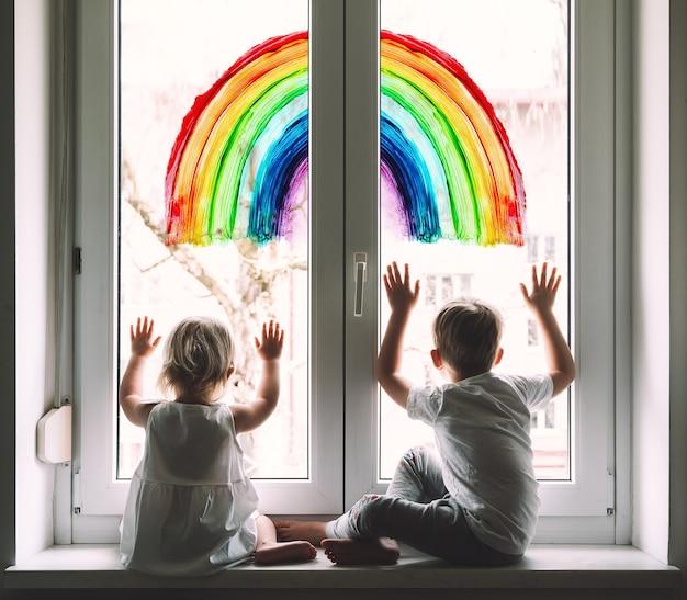 窓に虹を描く背景に小さな子供たちポジティブな視覚的サポート