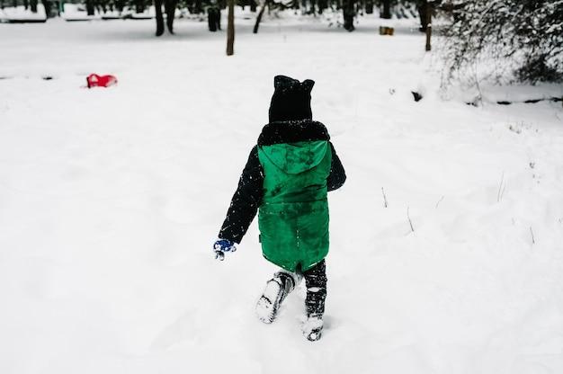 そりに乗って、ウィンターパークを歩いている小さな子供たち。その少年は両親と雪遊びをします。閉じる。肖像画の幸せな子供たち。
