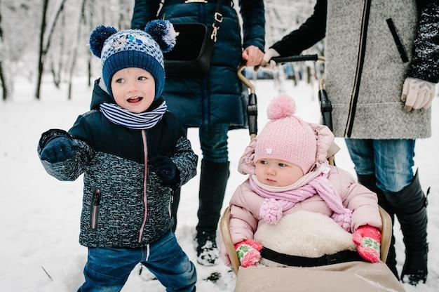 そりに乗って、ウィンターパークを歩いている小さな子供たち。男の子は女の子の近くを走ります。両親の背景に。閉じる。肖像画の幸せな子供たち。