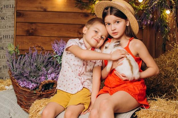 건초 배경에 토끼와 농장의 어린 아이들