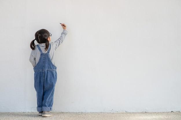白い壁に絵を描く小さな子供たち