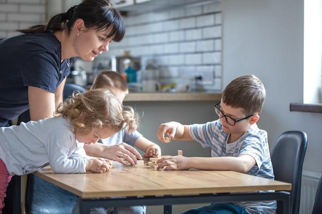 Маленькие дети играют в настольную игру с деревянными кубиками дома на кухне с мамой.