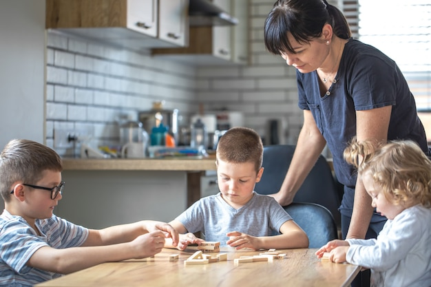 Little children play board game with wooden cubes at home in the kitchen with mom.