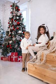 クリスマスツリーの近くで遊ぶ小さな子供たち