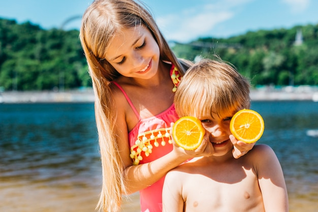 Little children playing with orange slices on beach