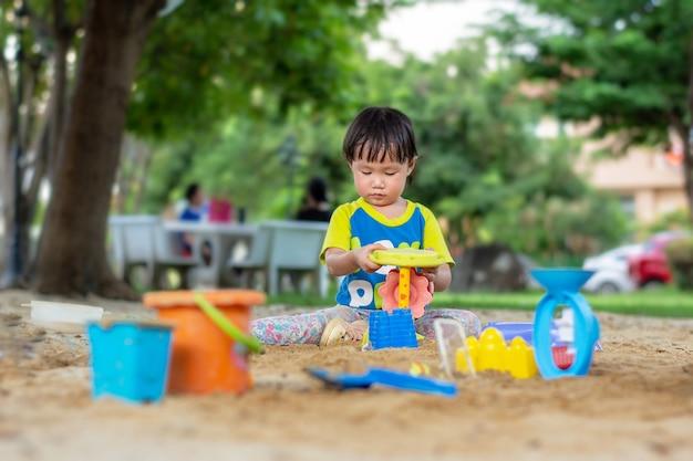 Маленькие дети играют с игрушками в песке на открытом воздухе