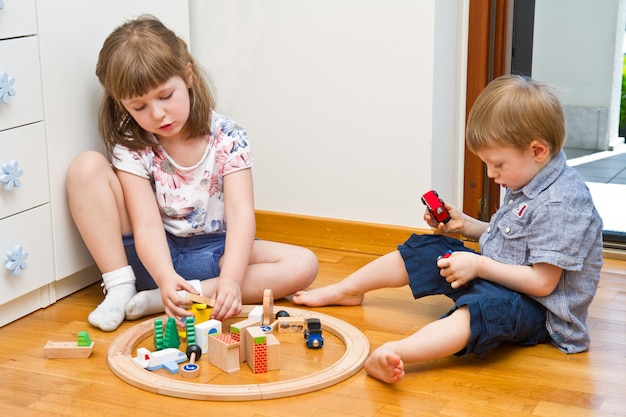 Little children playing with wooden train in the room