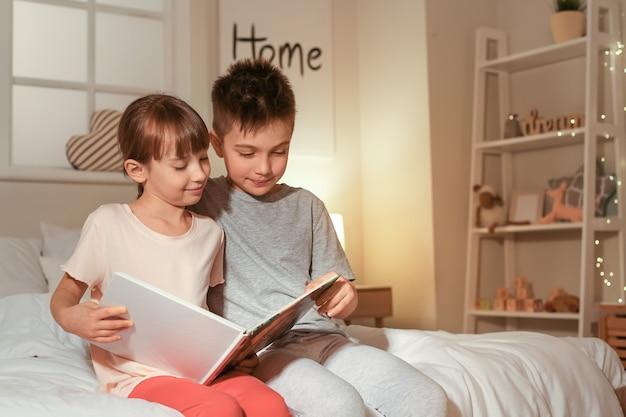 Маленькие дети читают сказку на ночь дома