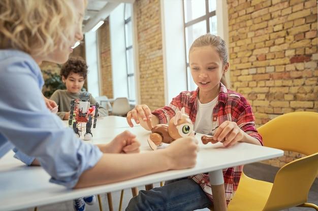 테이블에 앉아 기술 장난감을 살펴보고 웃고 있는 어린 아이들